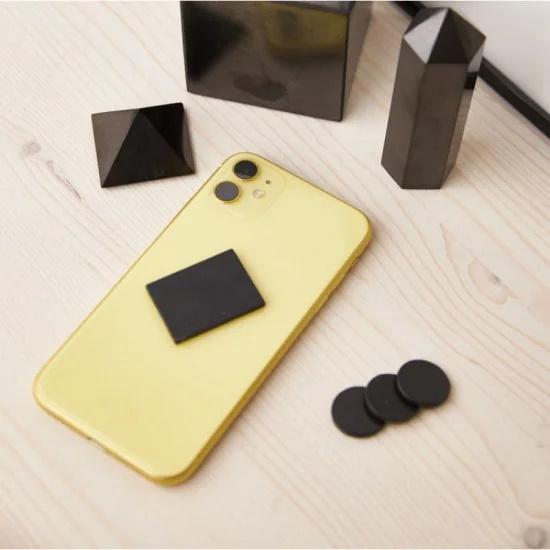 Polert shungitt brikke med klistremerke for mobiltelefoner. Beskyttelse mot EMF.